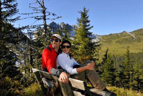 Wanderer sitzen auf einer Sitzbank im Zillertal