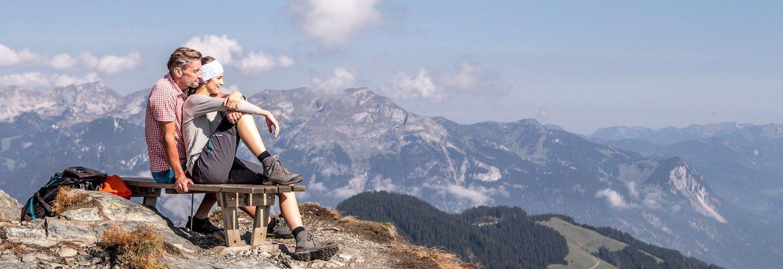 Wanderer machen Pause auf Sitzbank mit Bergpanorama