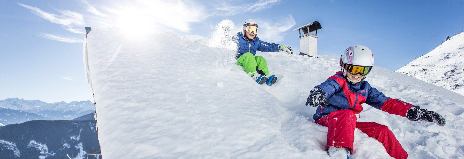 Kinder auf Dach Winterspaß Schnee