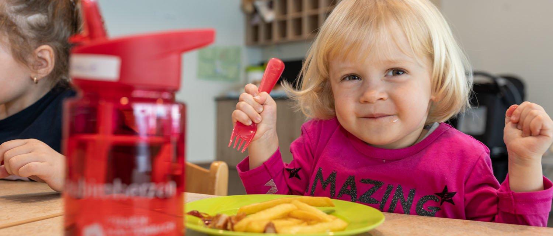 Kind beim Mittagessen im Gästekindergarten